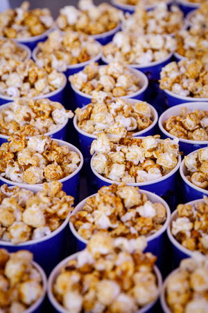 Many cups of popcorn before the movie. Side view, selective focus