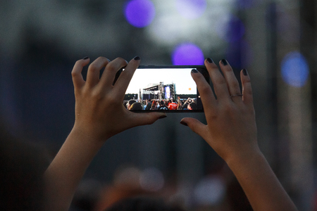 Smartphone in hand record outdoor music show.