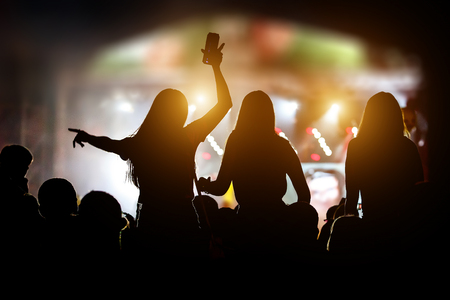 Silhouettes of girls at outdoor music show. Imagens