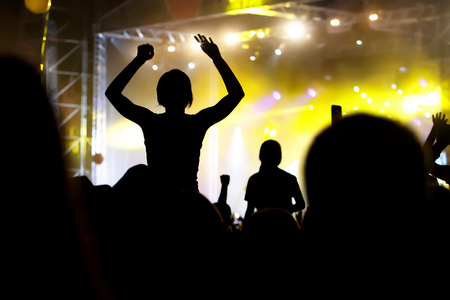 People silhouettes with raised hands at outdoor music show
