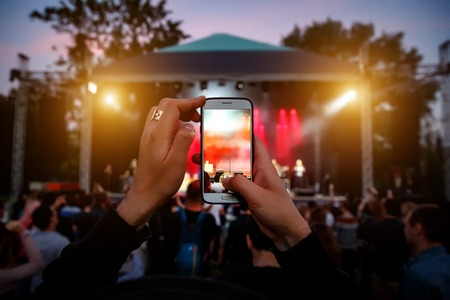 Hands with a smartphone records live music festival, Taking photo of concert stage Reklamní fotografie