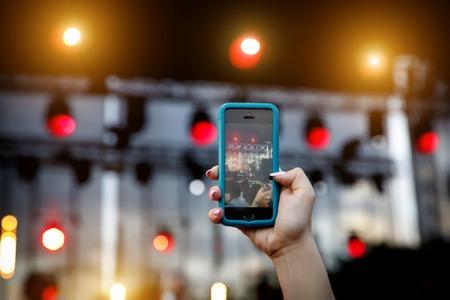 Using a mobile phone at outdoor summer music festival Reklamní fotografie - 122631717