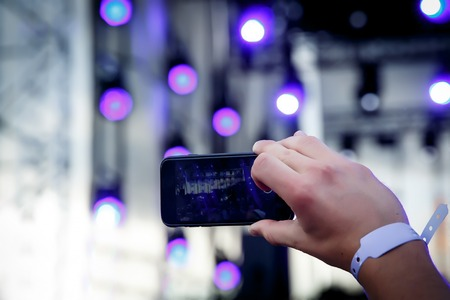Using a mobile phone at outdoor summer music festival