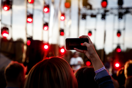 Using a mobile phone at a summer music show Reklamní fotografie - 122631724