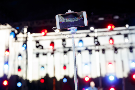The monopod with phone photographing a stage at a summer concert.