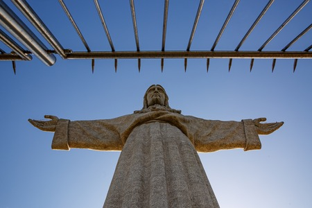 Statue of Christ in front of the iron fence, concept of struggle against religion Reklamní fotografie - 123711647