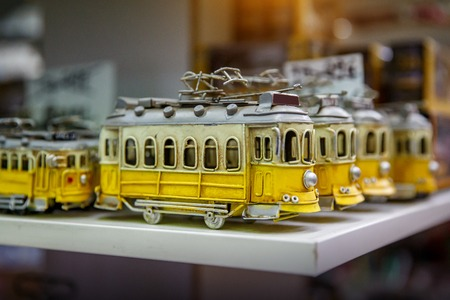 Symbol of Lisbon, a toy of the traditional yellow tram in souvenir shop Reklamní fotografie - 123712133