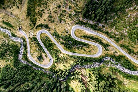 Winding road with a lot of turns, top view. Mountain river nearby 版權商用圖片