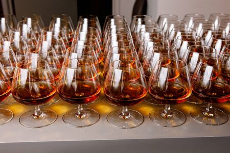 Stylish glasses with cognac or whiskey on table at event catering.
