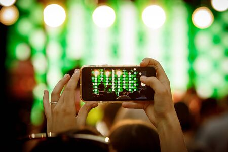 Mobile phone in hand during the shooting of a concert, light show