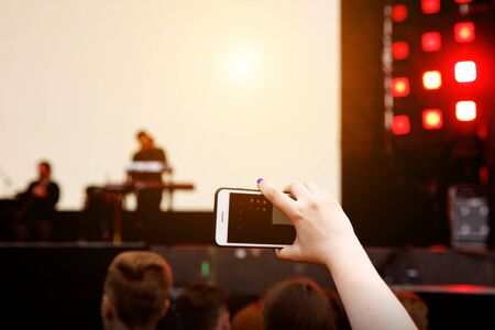 Video recording on a mobile phone, concert show Standard-Bild - 129484637