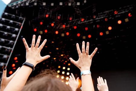 Hands of happy people. Crowd having fun in front of the stage