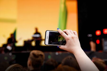 Video recording on a mobile phone, concert show Standard-Bild - 129484624