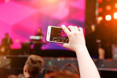Video recording on a mobile phone, concert show Standard-Bild - 129484629