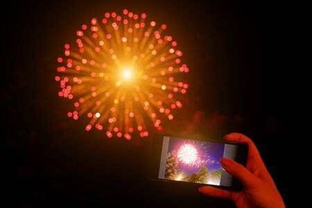 Shoots fireworks video on smartphone Фото со стока