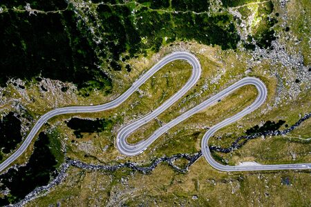 Aerial top view of serpentine narrow road. A road full of twists and turns winding. Romania Stock fotó - 129484293