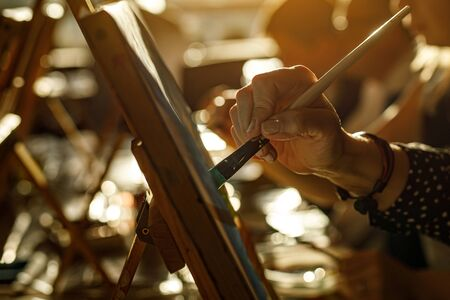 Hand of artist with brush painting picture, sunset light Standard-Bild - 129484111