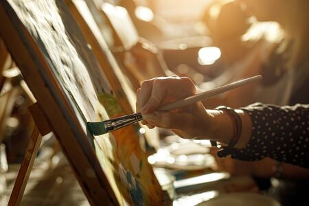 Hand of artist with brush painting picture, sunset light Standard-Bild - 129484112