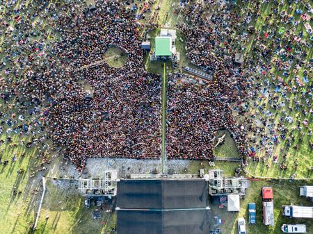 Crowd in front of a stage at a summer music festival. Top view