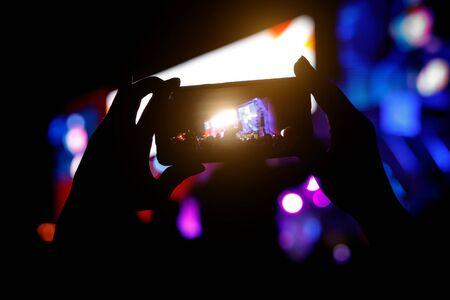 Silueta de smartphone en manos en un espectáculo musical. Rodaje de escenario