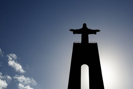 Christ statue silhouette in front of blue sky and clouds