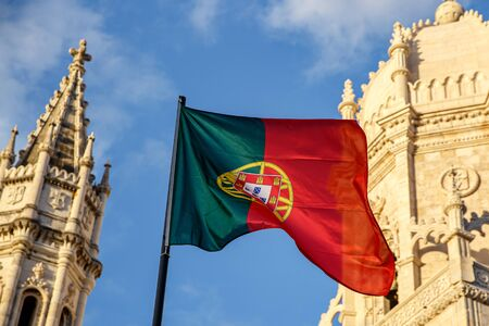 Portuguese flag waving in front of a blue sky and monastery Stock Photo