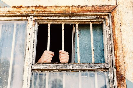 Hands of the prisoner on a steel lattice