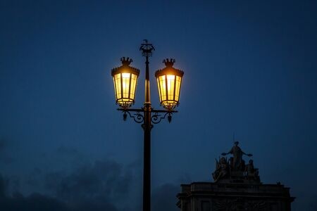Old fashioned street lamp at night. Magic lamp with a warm yellow light in the city twilight.