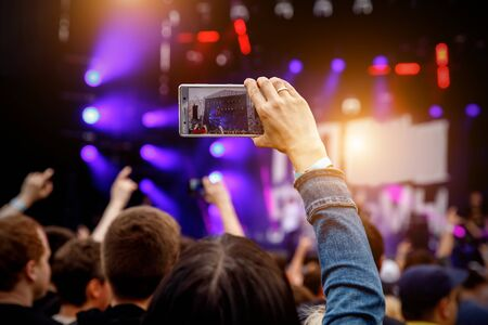 Recording concert by smartphone. Mobile phone in raised hands