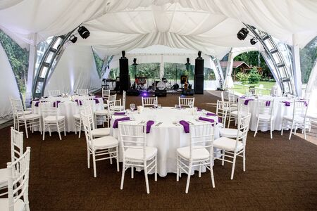 Interior of a event tent decoration ready for guests. Served round banquet table outdoor in marquee.
