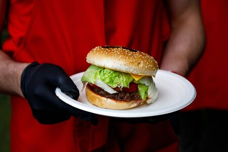 Man holds ready tasty burger in hands in black gloves.