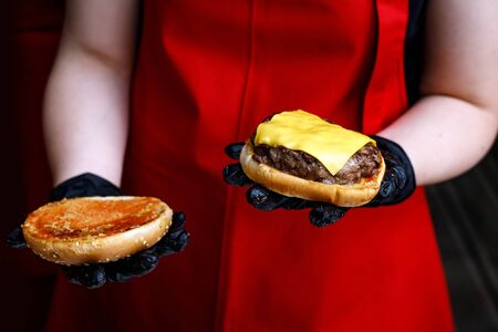 Chef makes a burger in black gloves. Picks up ingredients Stockfoto