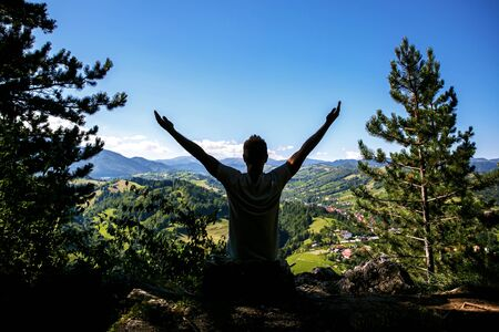 Happy Man raised hands in front of a beautiful green valley in the mountains. Travel lifestyle emotional concept