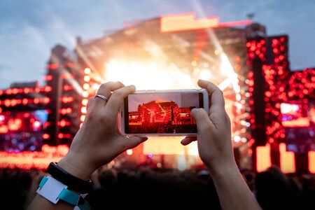 Using camera of mobile phone to take pictures and videos at outdoor live concert.
