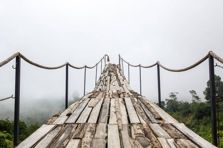 A wooden bridge over the jungle that breaks off at the end, Fog weather Stock Photo