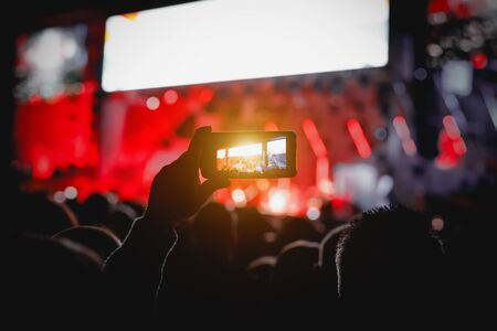 Smartphone in hands of fan during music show