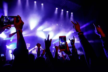 Crowd of people having fun while watching concert show at music festival. Raised hands with mobile phones Banco de Imagens
