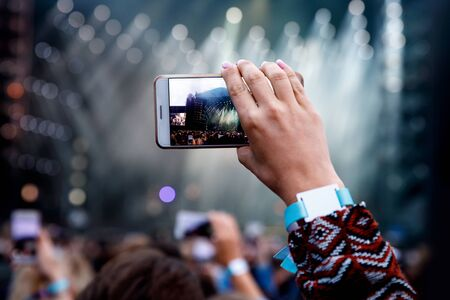 Man holding his smart phone and photographing concert