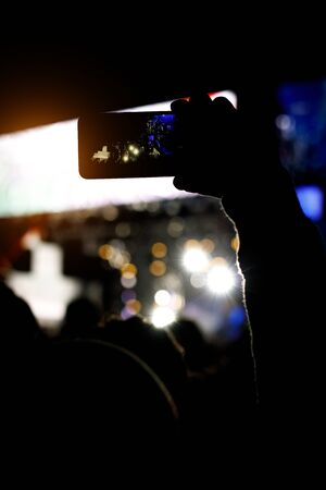 Silhouette of smartphone in hands of fan during music show Standard-Bild
