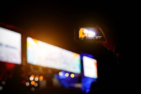 Silhouette of hands with a smartphone at a big music festival, video recording of stage show
