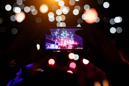 Hand of man taking the photo of fireworks by smartphone.