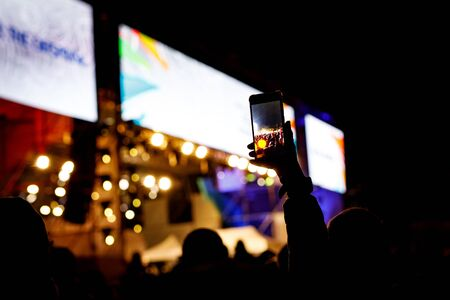 Silhouette of people holding their smart phones and photographing concert