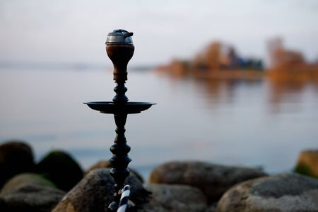 Top of hookah on nature. Sunset time and lake on background Imagens