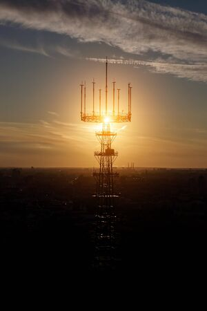 Communication tower on city and sunset background