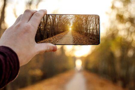 Verwenden eines Mobiltelefons. Macht ein Foto von einer herbstlichen Gasse Standard-Bild