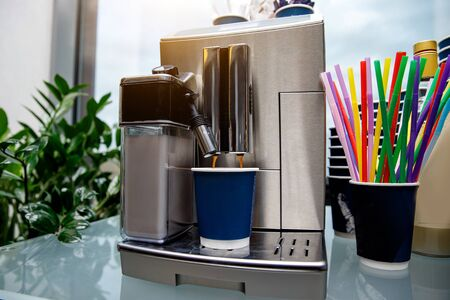 ?offee machine makes coffee. Plastic blue cup