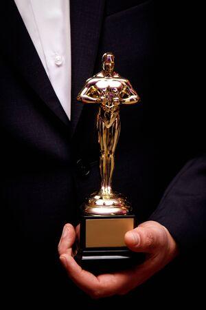 Figurine Oscar en mains. Gagnant tenant son prix Banque d'images