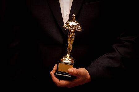 Figurine Oscar en mains. Gagnant tenant son prix