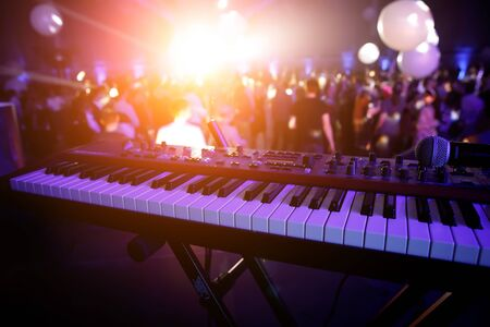 Piano keys in purple light on concert stage. Synthesizer