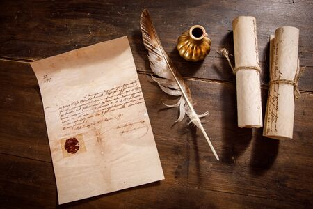 Quill pen, feather with a letter and a scroll on a wooden table. Vintage concept